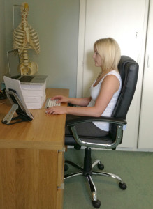 Safer: Using an external keyboard and mouse and raising the screen with paper reams improves this laptop workstation for Chiropractor Yvonne